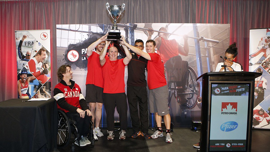 Team of 4 hold up the paratough cup (over their head) for photo; Josh Dueck in his chair beside presenting the award