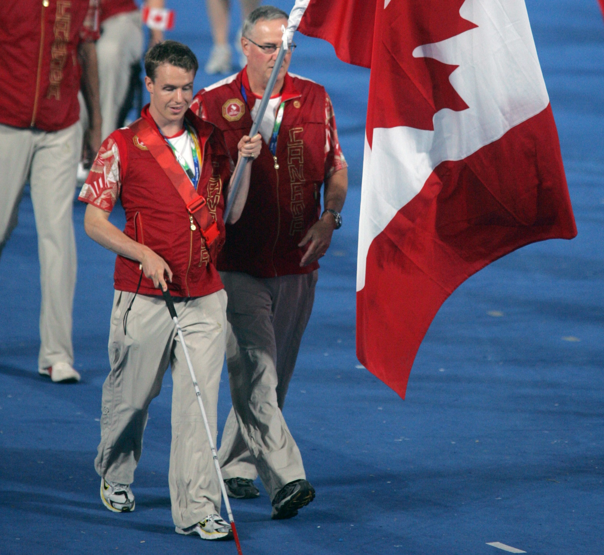 Para swimmer Donovan Tildesley, assisted by his father, waves the flag for Canada at the Opening Ceremony at Beijing 2008.