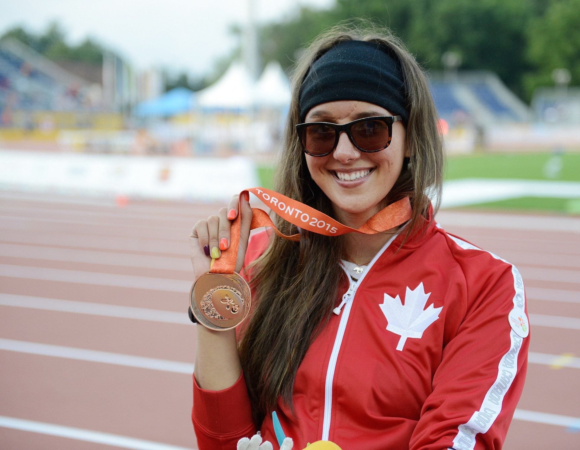 Pam LeJean holding her medal at Toronto 2015