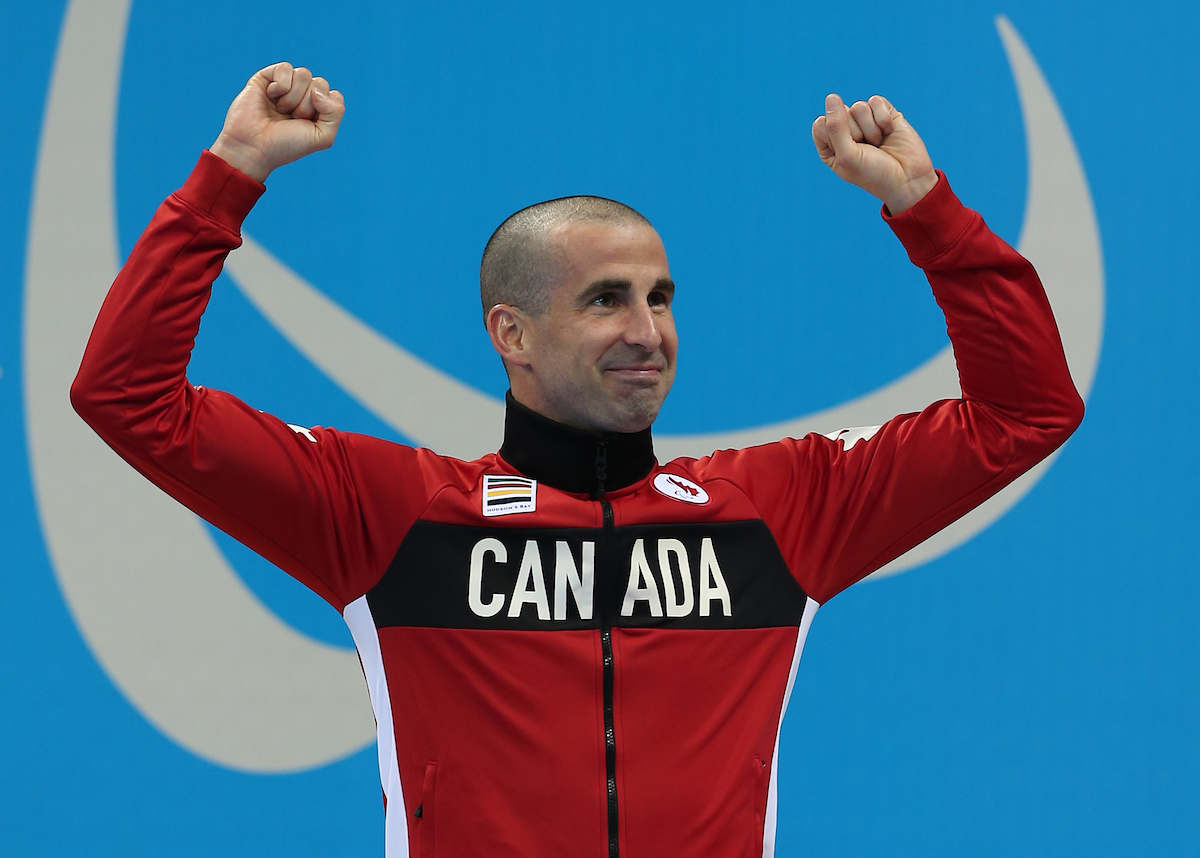 Benoit Huot with his arms in the air celebrating on the podium.