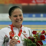 Stephanie Dixon wearing a gold medal holding flowers