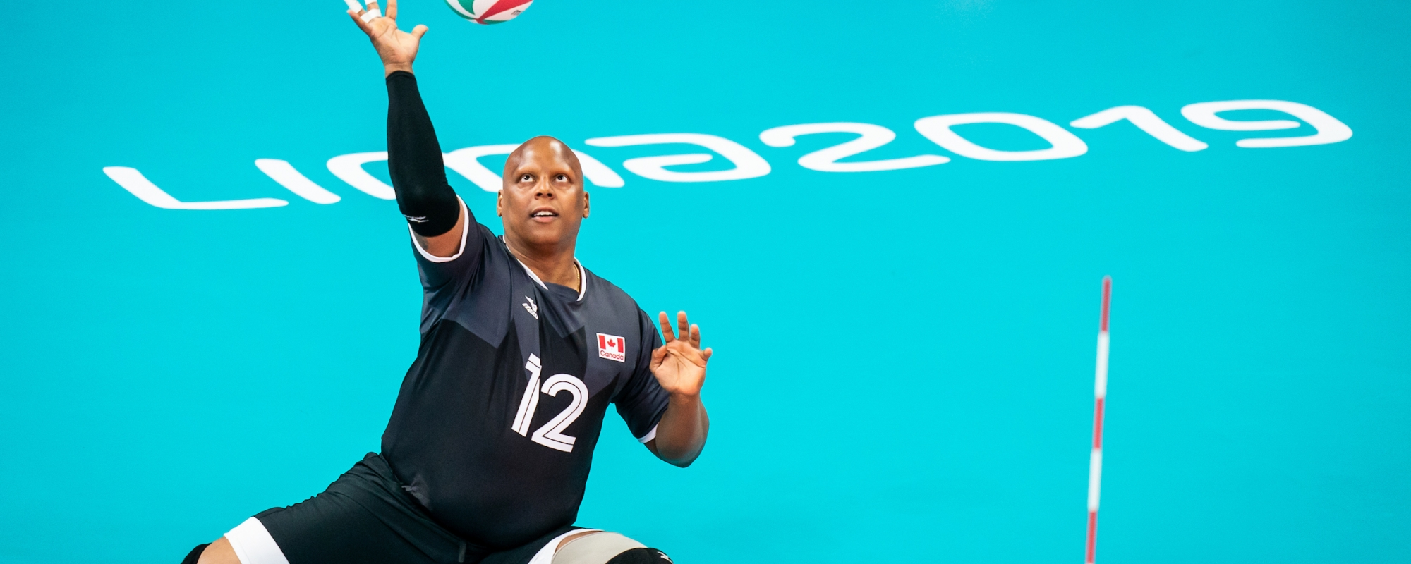 Jamoi Anderson serves in a game of sitting volleyball