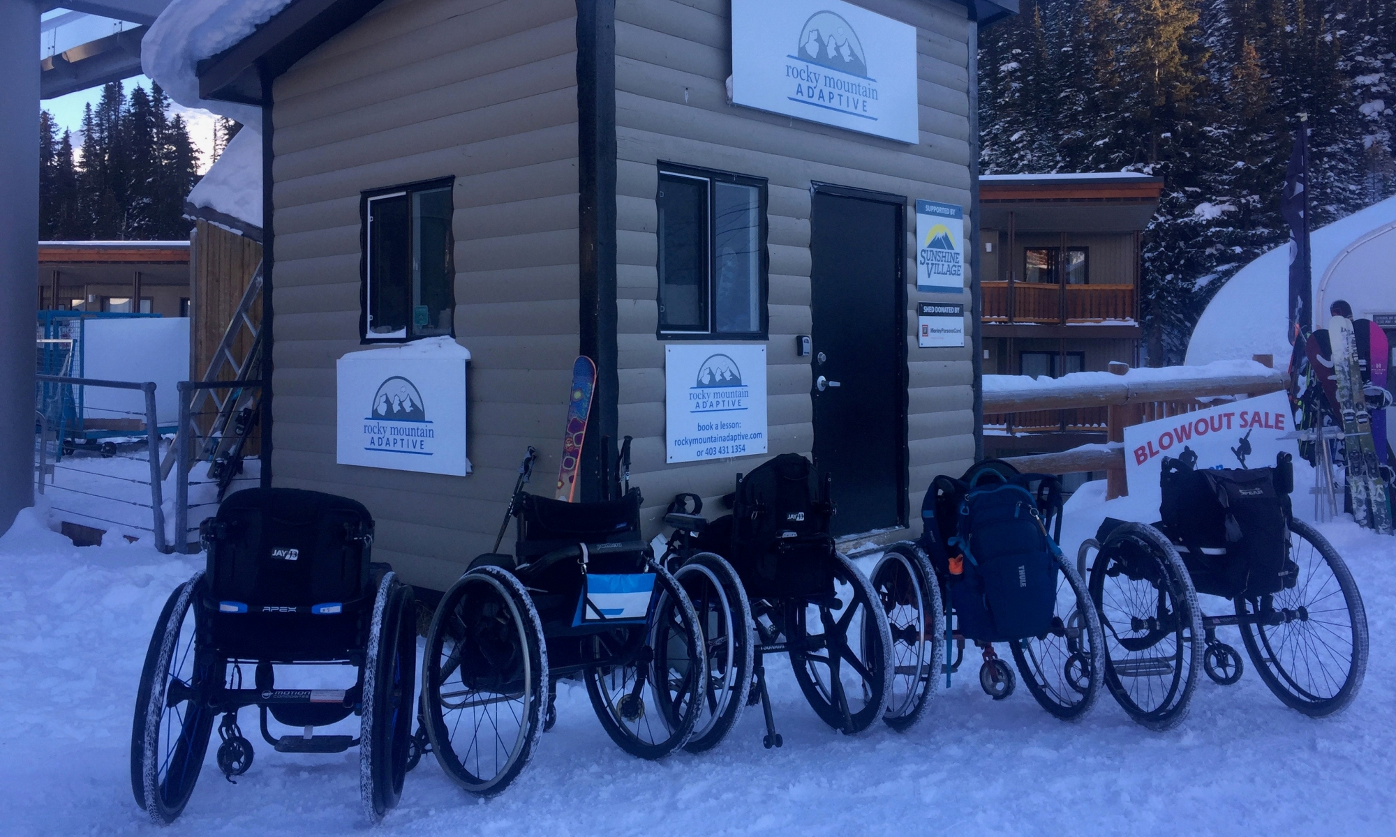 Wheelchairs in front of a skiing shed