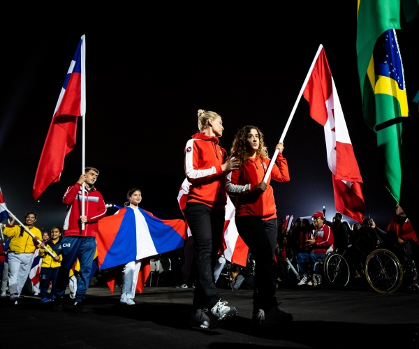 Carla Shibley and pilot Meghan Lemiski carry the flag at the Lima 2019 Closing Ceremony.