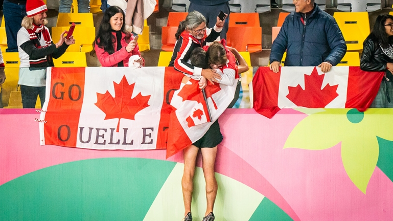 Guillaume Ouellet hugging his family with flags all around him