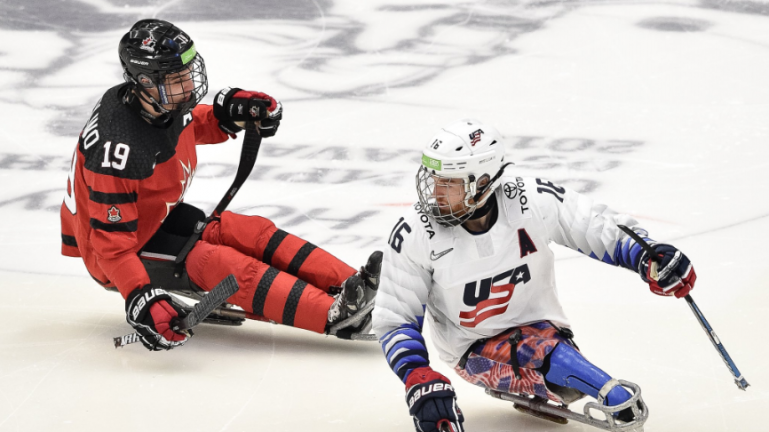 Dominic Cozzolino and an American player on the ice at the 2019 World Para Ice Hockey Championships