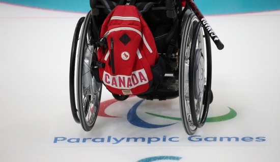 Wheelchair on curling ice with a team canada backpack