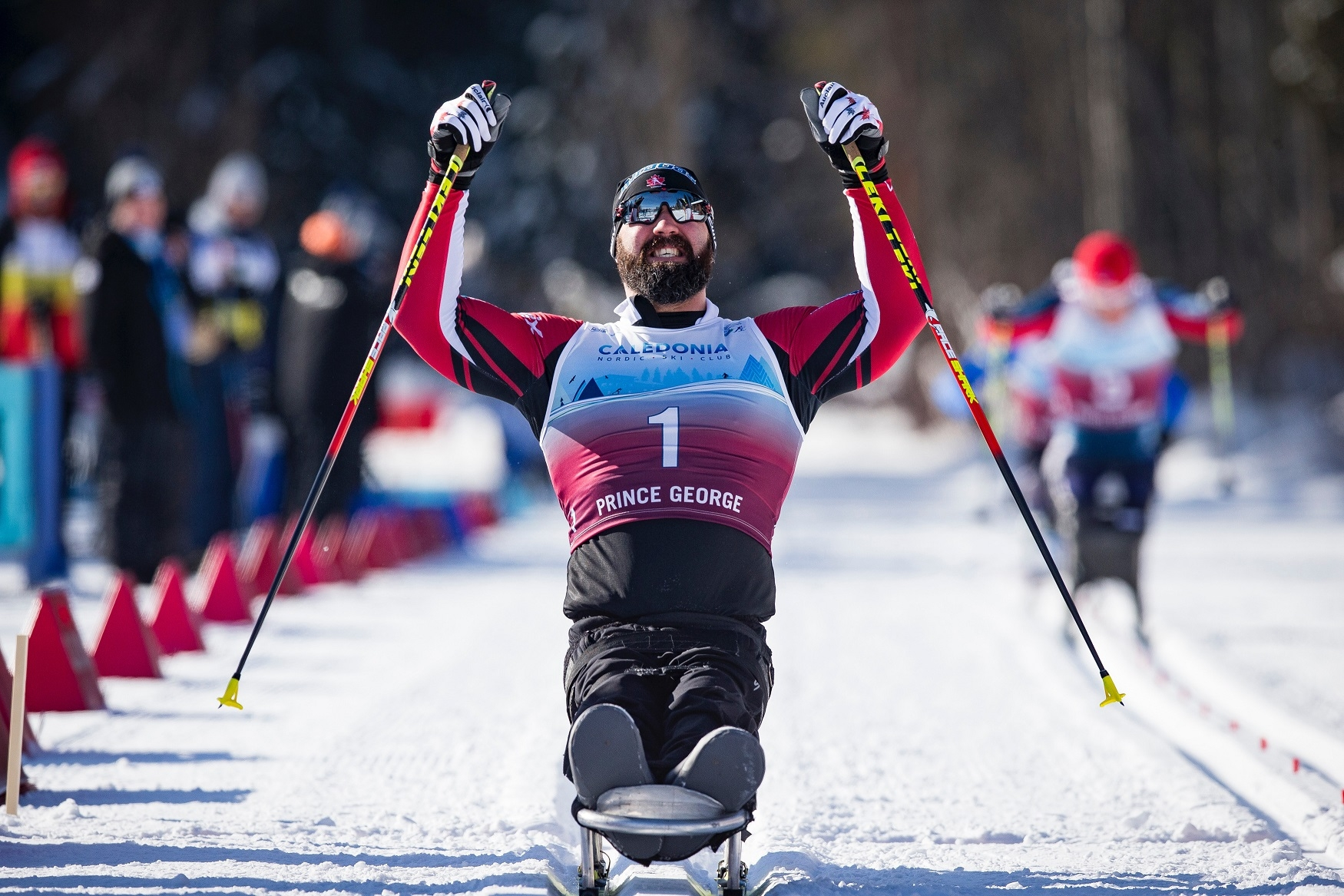 Collin Cameron raises his arms in victory at the 2019 World Para Nordic Skiing Championships
