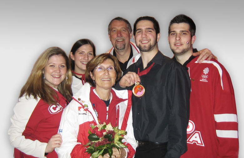 The Westlake family celebrating Canada's gold medal win at the Torino 2006 Paralympic Winter Games, Greg's first Paralympic Games. From left: Rachelle Westlake, Nicole Westlake, Deb Westlake, Jim Westlake, Greg Westlake, and Scott Westlake.