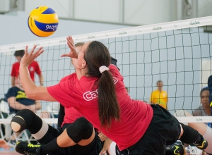 A sitting volleyball player in a Canada shirt hits the ball.